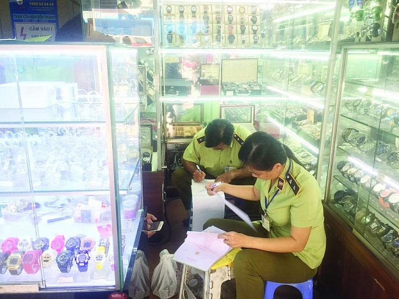 Lực lượng quản lý thị trường TPHCM lập biên bản xử lý vi phạm tại một điểm kinh doanh hàng giả hàng nhái tại chợ Bến Thành. Ảnh: N.H